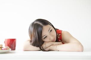 机の上に腕を組み顔を乗せる女性 FYI01076881