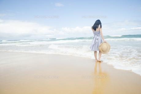 波打ち際で佇む黒髪の女性 FYI01076882