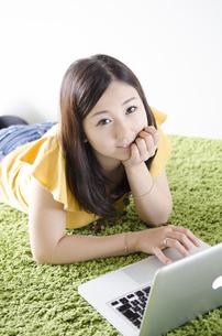 床に寝そべってノートパソコンを操作する女性 FYI01076883