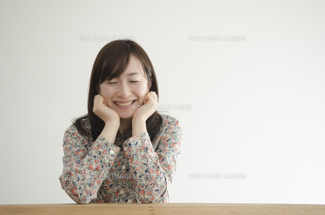机の上で頬杖を付いて笑う女性 FYI01076889