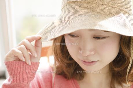 帽子をかぶってつばを触る女性 FYI01076893