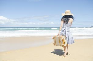 波打ち際をスーツケースを持って歩く女性 FYI01076898