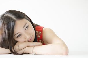 机の上に腕を組み顔を乗せる女性 FYI01076901