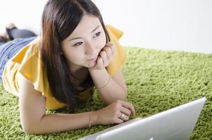 床に寝そべってノートパソコンを操作する女性 FYI01076906