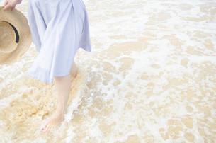波打ち際を歩く女性の足と帽子 FYI01076915