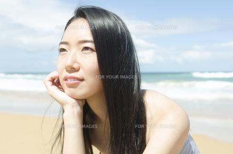 ビーチで頬杖を付いて遠くを見つめる黒髪の女性 FYI01076916