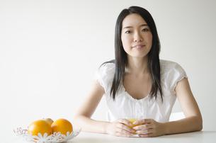 テーブルでオレンジジュースのコップを触る女性 FYI01076922