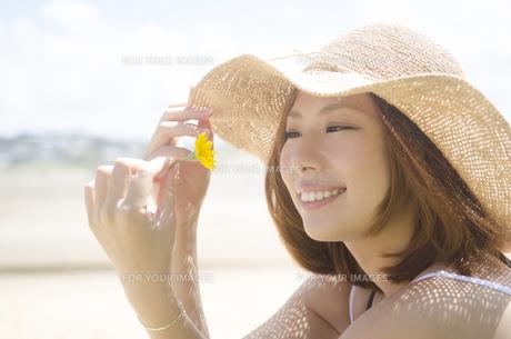 帽子を被り黄色い花を見つめる女性 FYI01076925