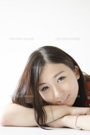 机の上に腕を組み顔を乗せて笑う女性 FYI01076929