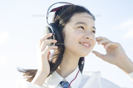 制服姿でヘッドフォンを着けた女の子 FYI01076931