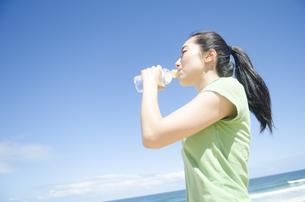 海をバックに水を飲む女性 FYI01076933