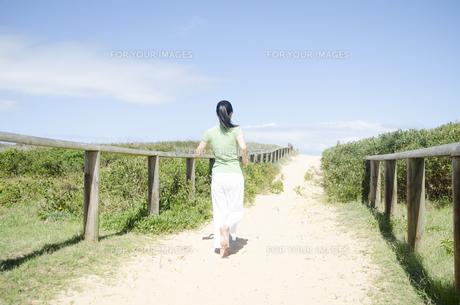ビーチでジョギングをするポニーテールの女性 FYI01076938