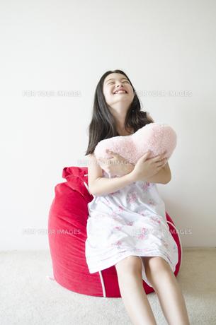 ハートのクッションを抱きしめるパジャマ姿の少女 FYI01076946