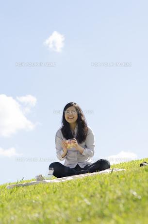 芝生の上でサンドイッチを持って笑顔の女性 FYI01076949