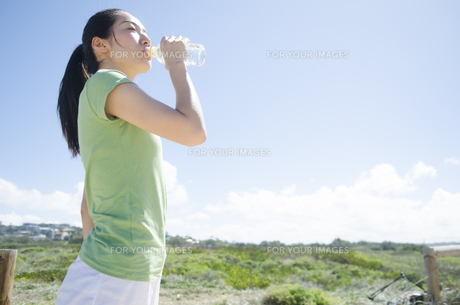 青空と緑をバックに水を飲む女性 FYI01076956