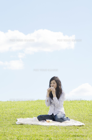 芝生の上でサンドイッチを食べる女性 FYI01076977