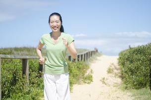 ビーチでジョギングをするポニーテールの女性 FYI01076979