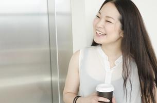 エレベーター前でコーヒーカップを持って笑うOL FYI01076984