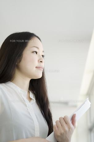 書類を手に持って遠くを見つめる女性 FYI01076987