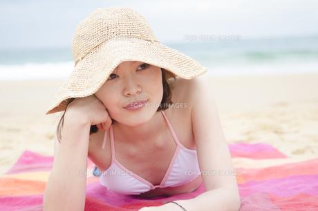 帽子をかぶってビーチに寝そべるビキニ姿の女性 FYI01076989