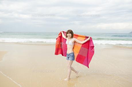 ビーチでタオルを広げて歩くビキニ姿の女性 FYI01076990