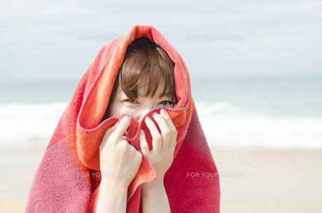 ビーチでタオルにくるまる女性 FYI01077015