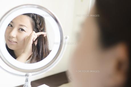 鏡を見ながら髪をいじる女性 FYI01077024