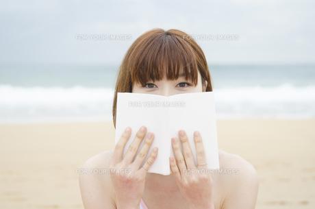 ビーチに座って本で顔を隠す女性 FYI01077027