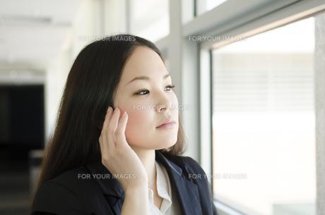 頬に手を添えて窓の外を見る女性 FYI01077029