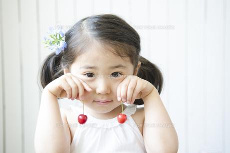 さくらんぼを涙の様にして持つ女の子 FYI01077030