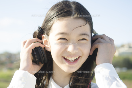 制服姿でヘッドフォンを着ける女の子 FYI01077040