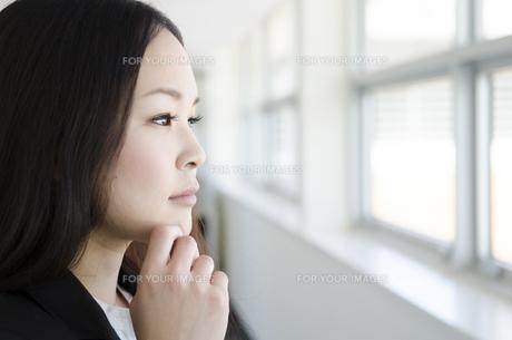 あごに手を添えて外を見る女性 FYI01077041