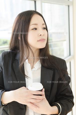 コーヒーカップを手にしたスーツ姿の女性 FYI01077047