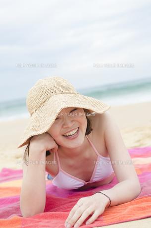 帽子をかぶってビーチに寝そべって笑うビキニ姿の女性 FYI01077051