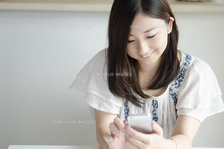 部屋の中でスマートフォンを操作する女性 FYI01077055