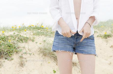 砂浜で水着の上から白いシャツを羽織った女性 FYI01077061