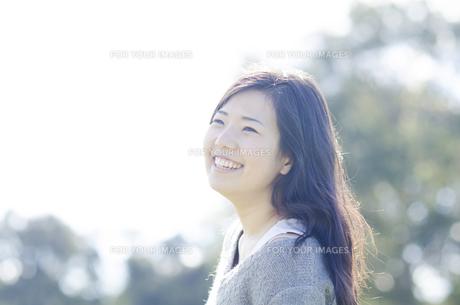 木をバックに笑顔の女性 FYI01077063