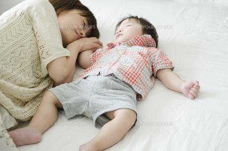 シーツの上で眠る男の子とお母さん FYI01077079