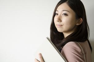 バッグを肩に掛けて本を持つ女性 FYI01077081