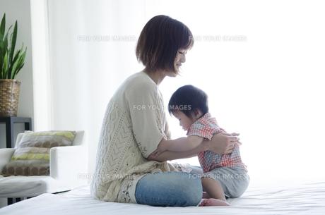 ベッドの上に座っている男の子とお母さん FYI01077085