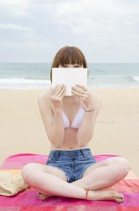 ビーチに座って本で顔を隠すビキニ姿の女性 FYI01077091