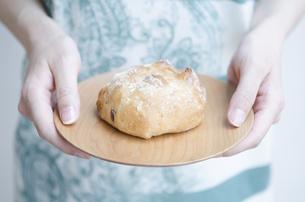 お皿に乗ったパンを持つ女性の手元 FYI01077092