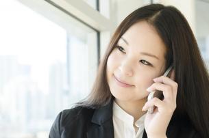 窓際で電話をするスーツ姿の女性 FYI01077094