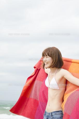ビーチでタオルを広げて笑うビキニ姿の女性 FYI01077095
