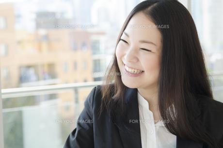 窓際で笑うスーツ姿の女性 FYI01077097