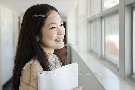 書類を抱えて廊下で笑うOL FYI01077106