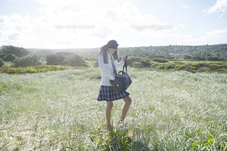 制服姿でヘッドフォンを着けて草原を歩く女の子 FYI01077111
