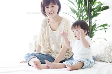 ベッドの上に座るお母さんと男の子 FYI01077117