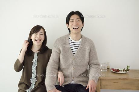 室内で並んで大笑いするカップル FYI01077118
