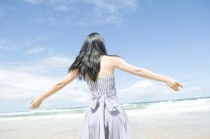 ビーチで手を広げる黒髪の女性 FYI01077127